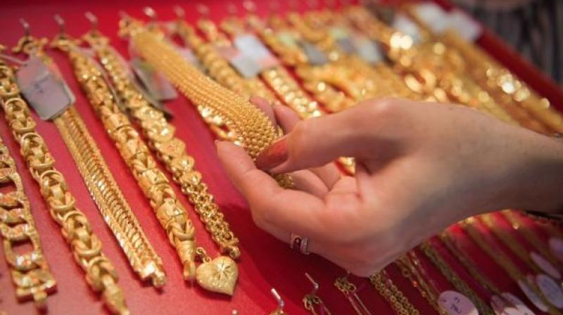 Gold prices were ruling almost flat at Rs 33,370 per 10 gram