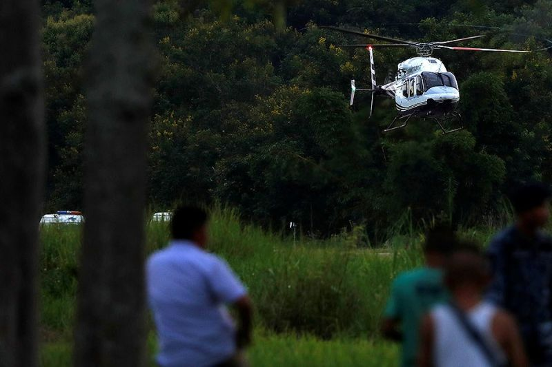 A helicopter carrying rescued schoolboys lands at a military airport