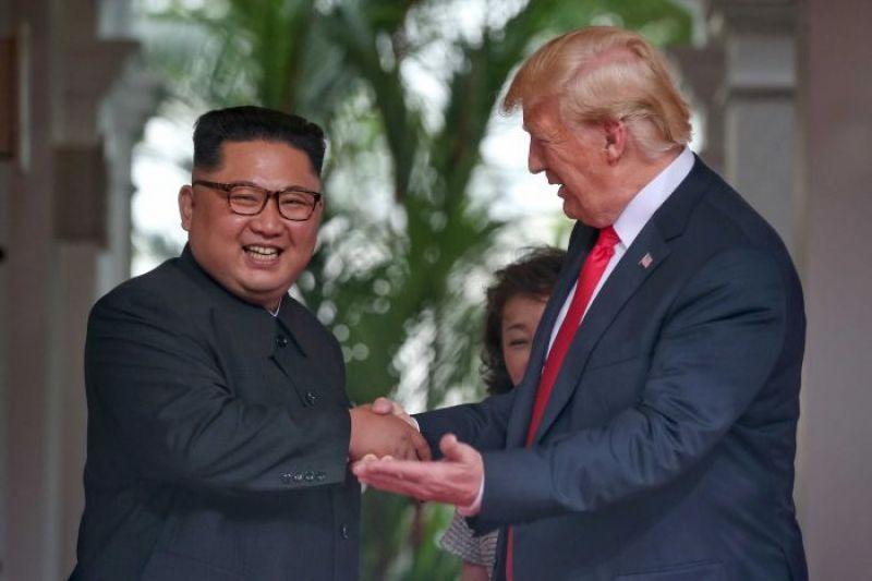 Donald Trump gestures as he talks to smiling Kim Jong-un