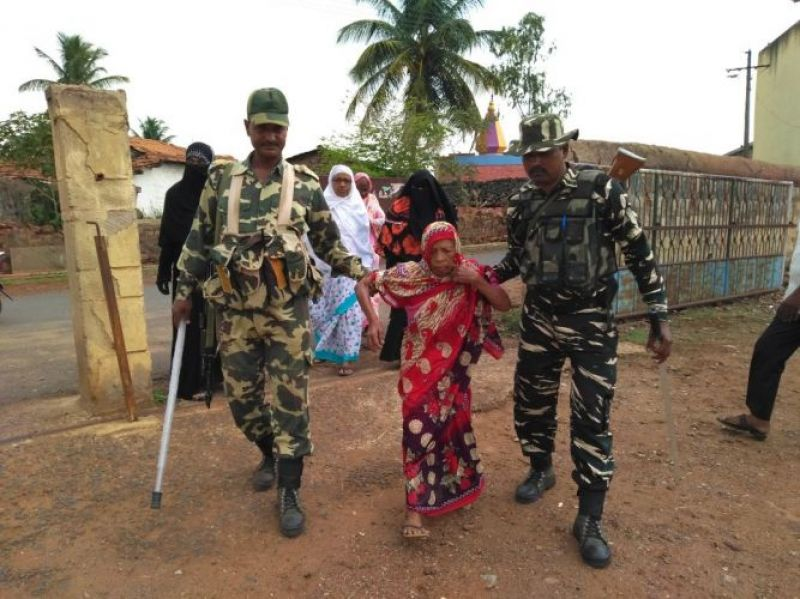 CRPF personnel helping a 90-year-old to reach out to the polling booth